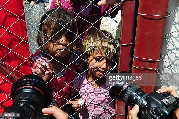 Photographers take photos of Syrian refugee children behind a fence on June 18 2011 in the Boynuyogun Turkish Red Crescent camp in the Altinozu...