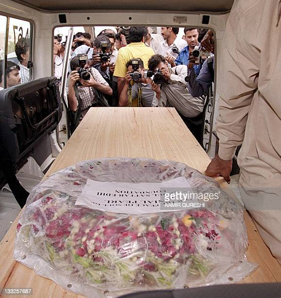 Photographers take photos of the coffin of slain US reporter Daniel Pearl in Karachi, 07 August 2002. An armed police convoy escorted the remains of...