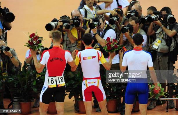 Photographers take picture of track cyclists Joan Llaneras of Spain , Roger Kluge of Germany and Christopher Newton of Great Britain as they stand on...