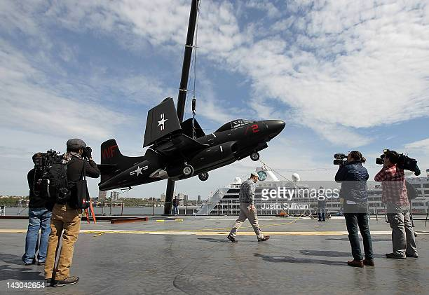 Photographers take pictures as a Douglas F3D2 Skyknight is lifted from the flight deck of the USS Intrepid on April 18 2012 in New York City In order...