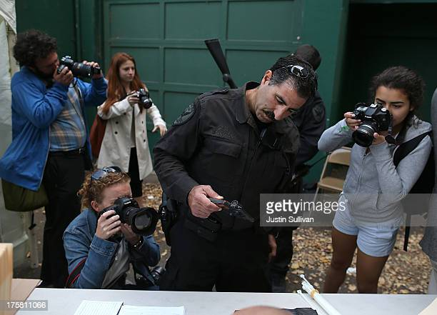 Photographers take pictures as San Francisco police officer Nicholas Shihadeh inspects a surrendered firearm during a gun buyback event on August 8...