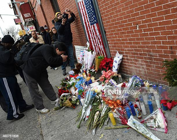 Photographers take pictures at a memorial near Tompkins Ave and Myrtle Ave December 21 2014 in New York near the site where two New York City police...