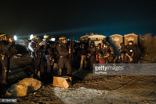 Photographers take pictures in the Calais Jungle in Calais France of a group of police men during clashes with the migrants and the police on 23...