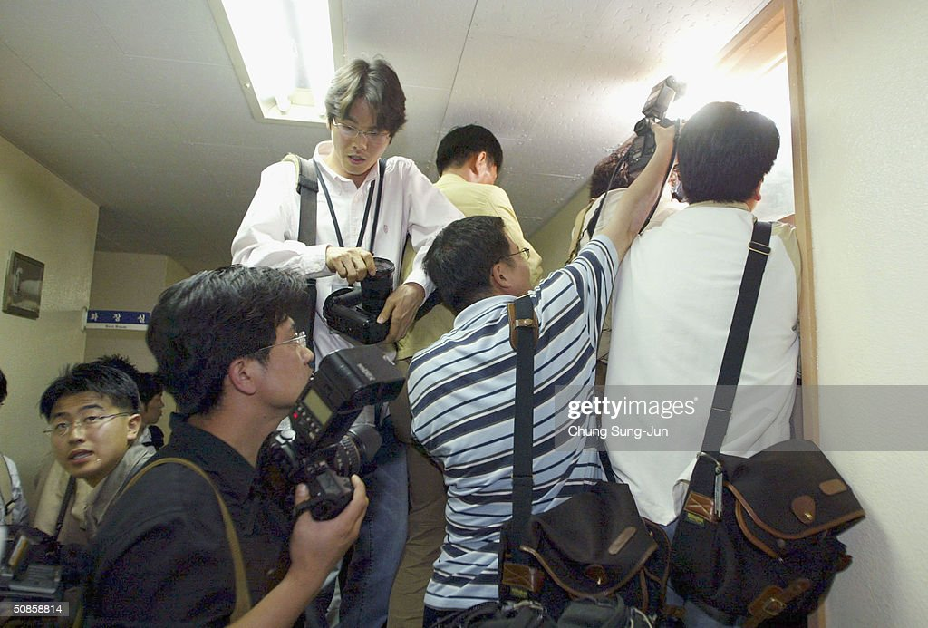 Photographers take pictures in the window where the Investigator's from the United States Forces Korea (USFK) and South Korean investigator speak at the police station on May 20, 2004 in Seoul South, Korea. Five U.S. soldiers and one Korean soldier were arrested on May 15, following an attack on a 27-year-old civilian who had tried to stop the soldiers from making a disturbance in the area, the unidentified victim underwent surgery on his neck at a nearby hospital and remains in a non-critical condition.