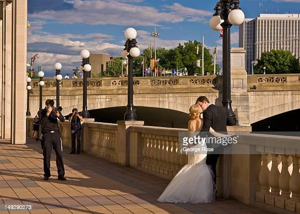 Photographers take pictures of a newly married couple outside the Fairmont Chateau Laurier Hotel on June 30 2012 in Ottawa Canada Ottawa the captial...