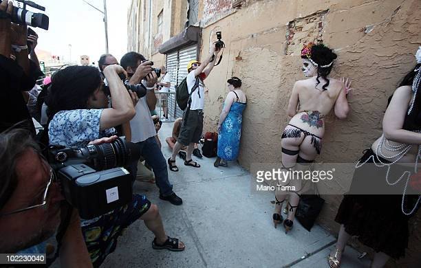 Photographers take pictures of a participant waiting to march in the 2010 Mermaid Parade at Coney Island June 19 2010 in the Brooklyn borough of New...