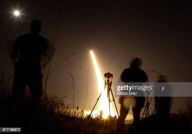Photographers take pictures of a streak of light trailing off into the night sky as the US military test fires an unarmed intercontinental ballistic...