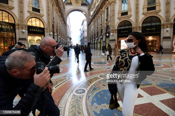 Photographers take pictures of a tourist wearing a protective face mask in Galleria Vittorio Emanuele II in the centre of Milan on February 28 after...