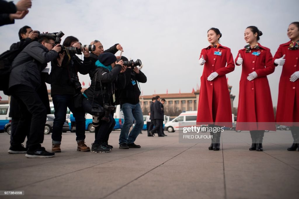 TOPSHOT - Photographers take pictures of Chinese hostesses in Tiananmen square during the opening session of the National People's Congress, China's legislature, in Beijing on March 5, 2018. Thousands of Chinese legislators erupted into enthusiastic applause over plans to give President Xi Jinping a lifetime mandate to mould the Asian giant into a global superpower. /