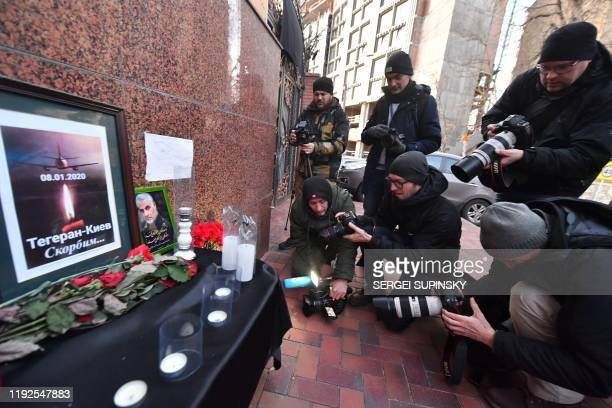 Photographers take pictures of flowers candles and a placard reading TehranKiev We mourn placed outside the Iranian embassy in Kiev on January 8 in...