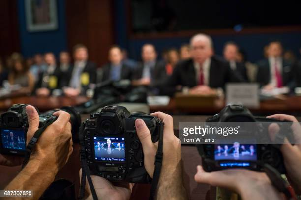 Photographers take pictures of former CIA director John Brennan testify before the House Permanent Select Committee on Intelligence in the Capitol...