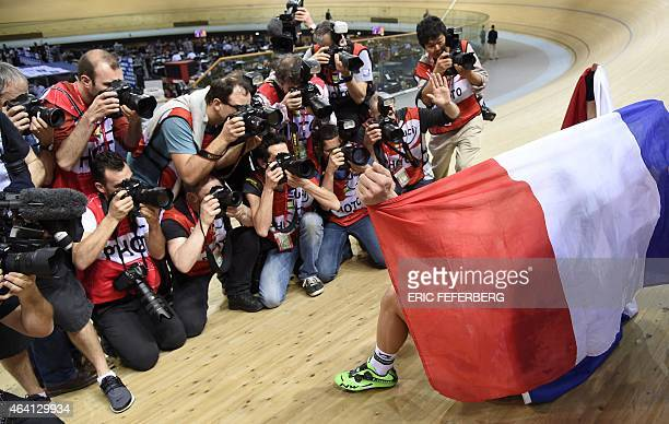 Photographers take pictures of France's Bryan Coquard and Morgan Kneisky draped with a French flag after they won gold in the Men's Madison final at...
