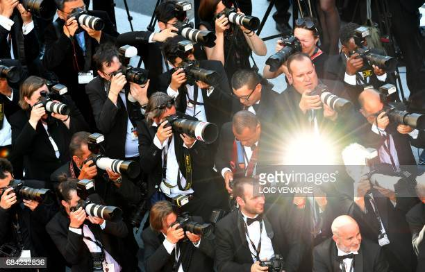 Photographers take pictures of guests arriving on May 17 2017 for the screening of the film 'Ismael's Ghosts' during the opening ceremony of the 70th...