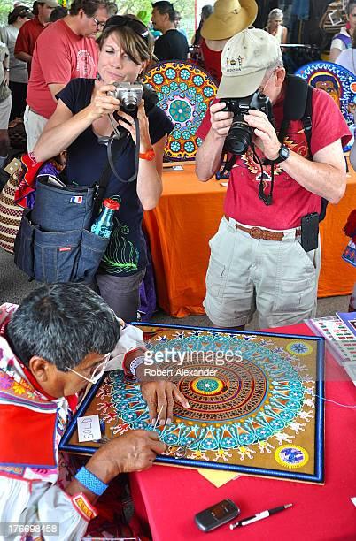 Photographers take pictures of Huichol Indian yarn painter Mariano Navarro from Mexico at the International Folk Art Market in Santa Fe New Mexico...