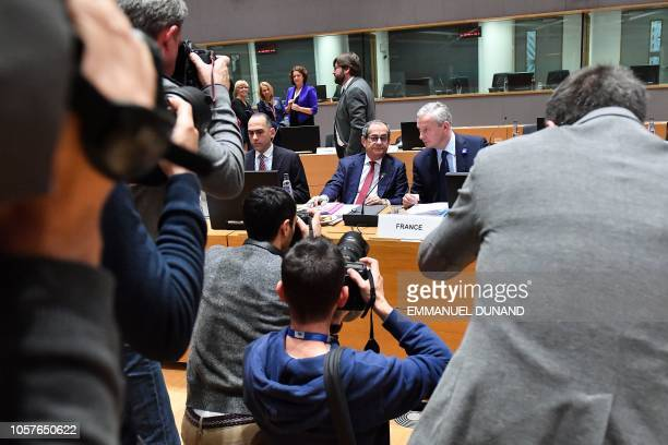Photographers take pictures of Italy's Finance Minister Giovanni Tria speaking with France's Finance Minister Bruno Le Maire while they attend a...