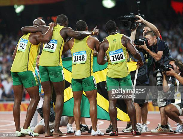 Photographers take pictures of Jamaica's Asafa Powell Usain Bolt Michael Frater and Nesta Carter as they celebrate after winning the men's 4100m...