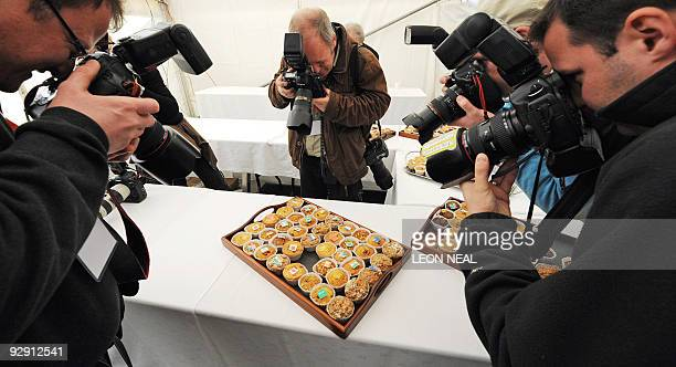 Photographers take pictures of muffins decorated with the flags of the G20 countries at the South Lodge Hotel in Horsham on the second day of the G20...