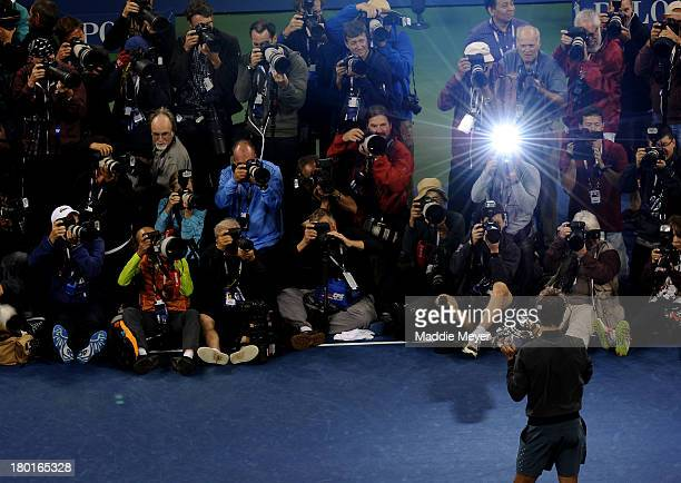 Photographers take pictures of Rafael Nadal of Spain as he poses with the US Open Championship trophy after winning the men's singles final match...