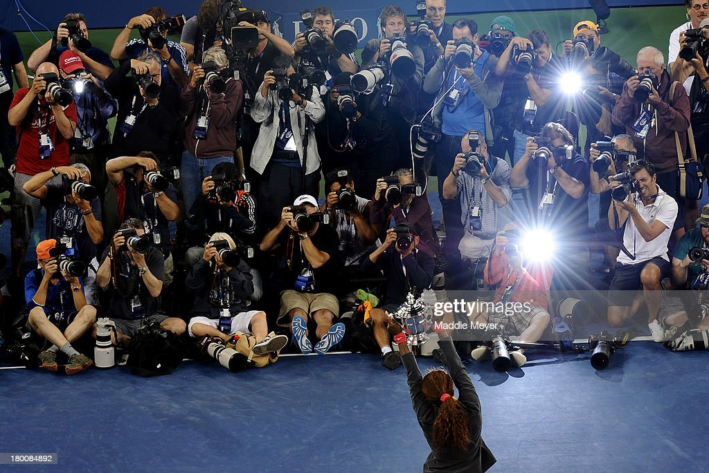 Photographers take pictures of Serena Williams of the United States of America smiles as she poses with the trophy after winning her women's singles final match against Victoria Azarenka of Belarus on Day Fourteen of the 2013 US Open at the USTA Billie Jean King National Tennis Center on September 8, 2013 in the Flushing neighborhood of the Queens borough of New York City.