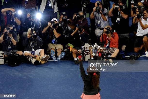 Photographers take pictures of Serena Williams of the United States of America smiles as she poses with the trophy after winning her women's singles...