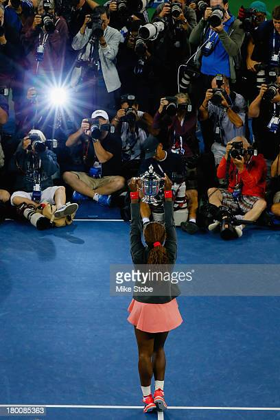 Photographers take pictures of Serena Williams of the United States smiles as she poses with the trophy after winning her women's singles final match...