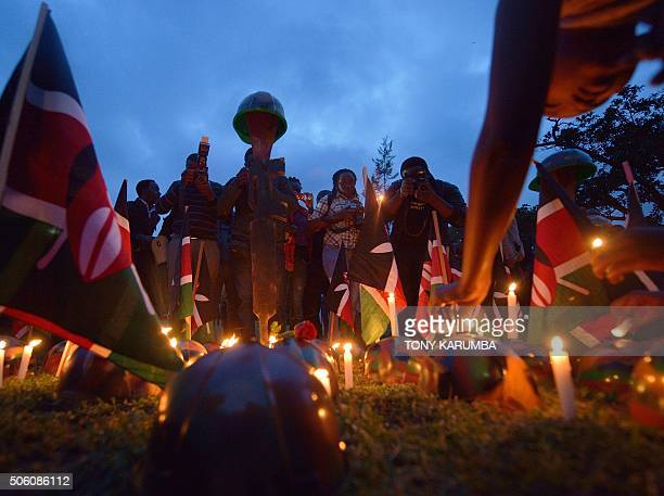 Photographers take pictures of symbolic helmets and Kenyan flags at a candle light vigil on January 21 2015 in Nairobi in honour of Kenya Defence...