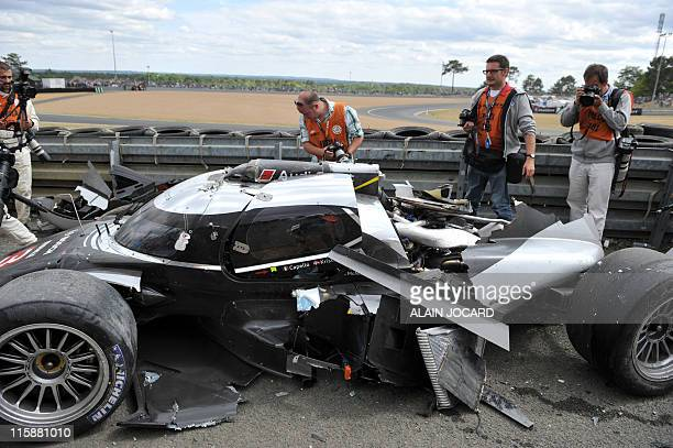 Photographers take pictures of the Audi R18 number 3 of Scottish driver Allan McNish after he crashed on the thirteenth round during the 79th edition...