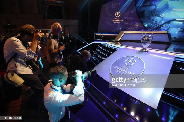 Photographers take pictures of the Champions League Trophy during the UEFA Champions League football group stage draw ceremony in Monaco on August...