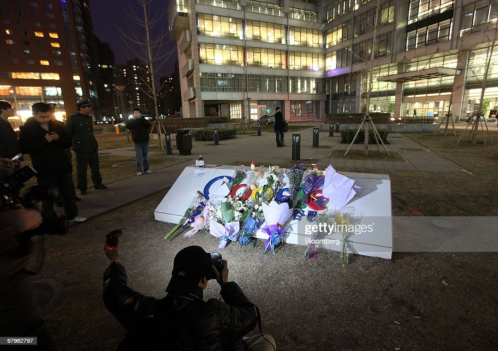Photographers take pictures of the flowers collecting outside the Google Inc. offices in Beijing, China, on Tuesday, March 23, 2010. Google Inc., following through on a pledge to stop censoring search results in China, began serving mainland Chinese users via its unfiltered Hong Kong site, a move that could prompt the government to block the service. Photographer: Doug Kanter/Bloomberg via Getty Images