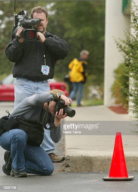 Photographers take pictures of the spot where a man was reportedly shot in the parking lot of a Ponderosa restaurant where a suspected sniper...