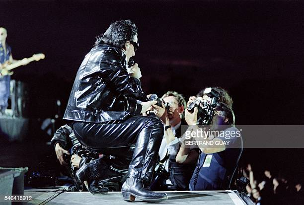 Photographers take pictures of U2 singer Bono as he performs during the U2 concert at Vincennes racetrack on June 26 part of the U2 'Zoo TV Tour' /...