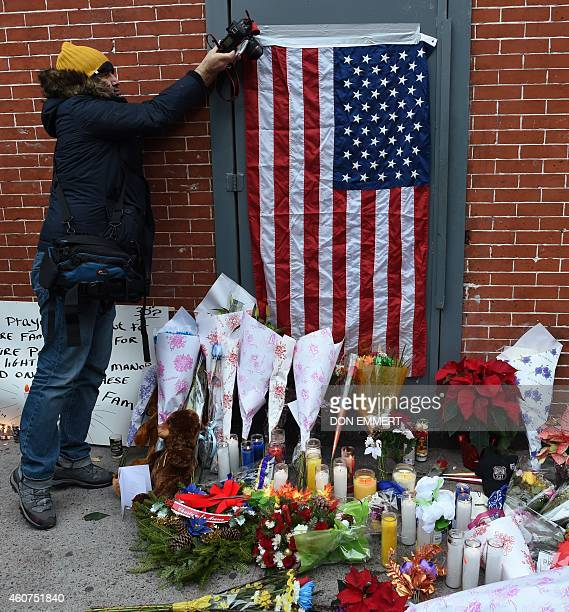 A photographers takes pictures at a memorial near Tompkins Ave and Myrtle Ave December 21 2014 in New York near the site where two New York City...