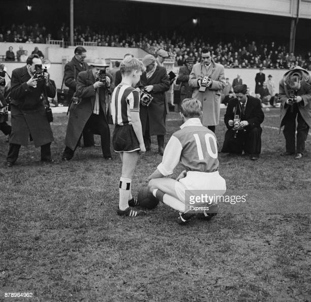 Photographers taking a picture of British football player George Eastham of Arsenal FC with a young fan wearing the Newcastle FC uniform at Highbury...