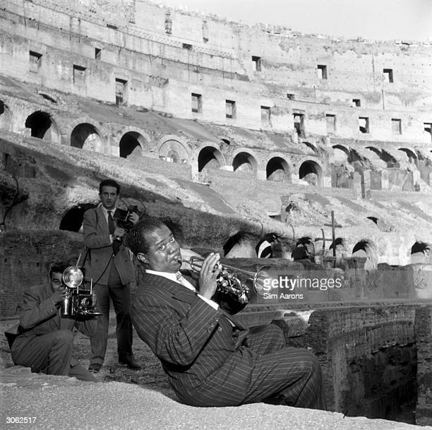 Photographers taking pictures of American jazz trumpeter and singer Louis Armstrong as he plays his trumpet in the Colosseum Rome