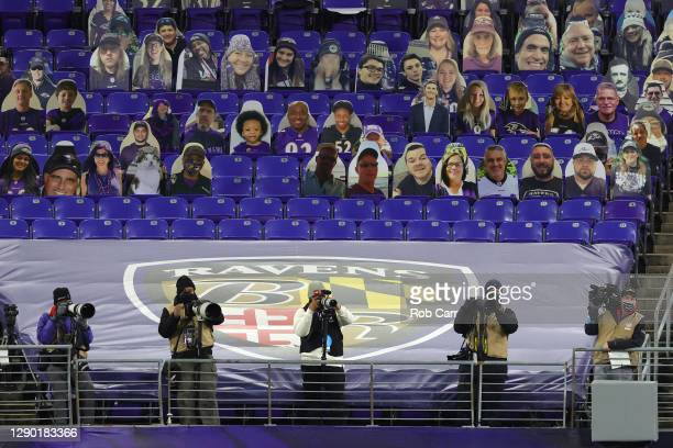 Photographers wear face coverings in front of cardboard cutouts of fans as the Dallas Cowboys play against the Baltimore Ravens during the second...