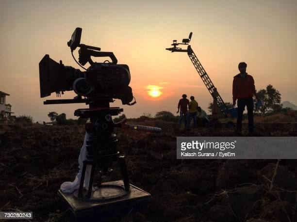 Photographers With Photographic Equipment On Field Against Sky During Sunset