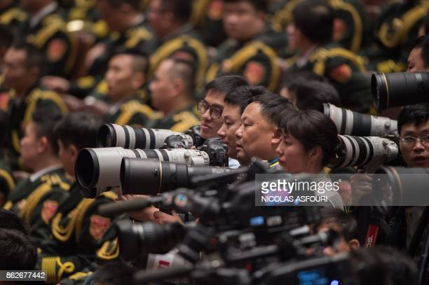 Photographers work as Chinese President Xi Jinping's delivers his address at the opening of the 19th Communist Party Congress at the Great Hall of...