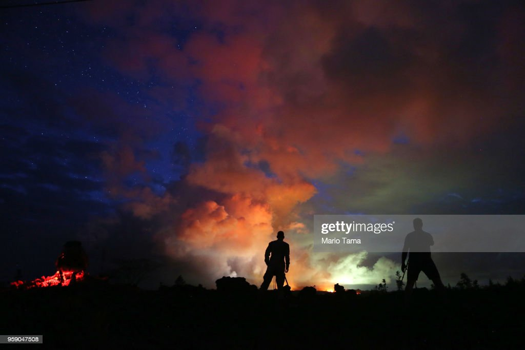 Photographers work as lava from active fissures illuminates volcanic gases from the Kilauea volcano on Hawaii's Big Island on May 15, 2018 in Hawaii Volcanoes National Park, Hawaii. The U.S. Geological Survey said a recent lowering of the lava lake at the volcano's Halemaumau crater 'has raised the potential for explosive eruptions' at the volcano.