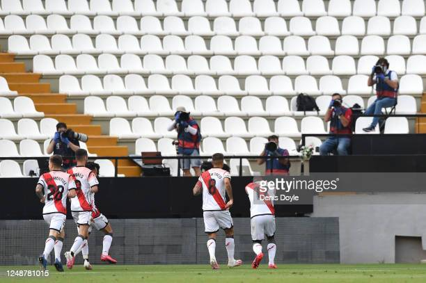 Photographers work on an empty stand as Luis Advincula of Rayo Vallecano celebrates with his team mates after scoring his team's first goal during...