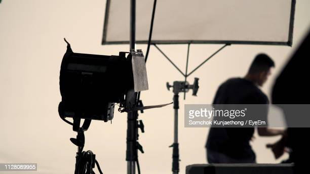 photographic equipment behind man standing in studio - film crew stock pictures, royalty-free photos & images