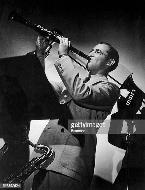 Photographic impression of Benny Goodman, who, with his clarinet, leads his orchestra through intricate swing rhythms on his Swing School broadcasts...