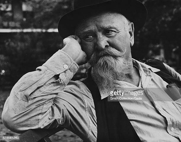 A photographic portrait of a mature sailor sitting on a park bench wearing a button down shirt vest and a hat with a mustache and goatee a portion of...