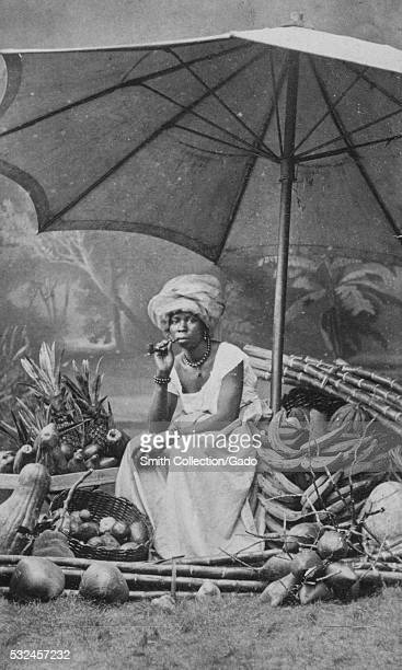 Photographic portrait of a woman sitting on a chair among various tropical fruits and vegetables, the woman is wearing a floor length white dress and...