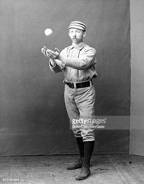 A photographic portrait of Arthur Irwin wearing a Philadelphia Quakers uniform in the photograph he is standing inside a studio and catching a ball...