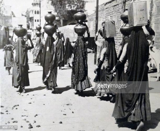 Photographic print of barefoot Chuddardraped Water Bearers Trudging Homeward in a Burning Sun Dated 20th Century