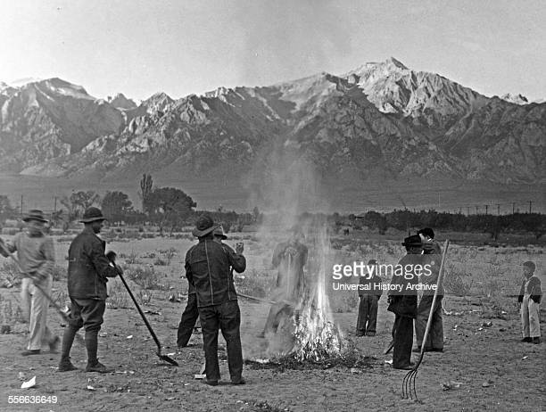 Photographic print of men and boys standing around a small brush fire holding shovels a pitchfork stands in the right foreground mountains in...