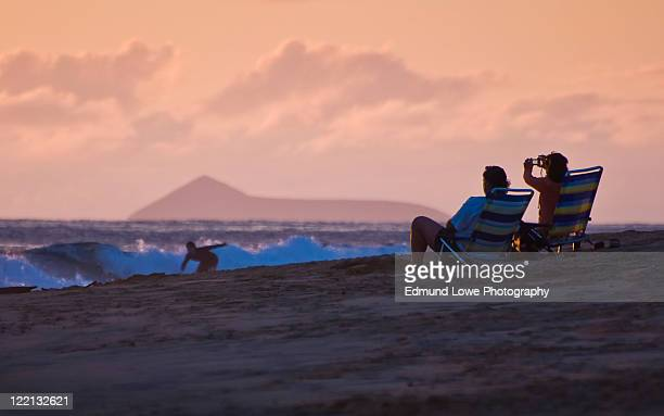 Photographing surfer at sunset, Kauai, Hawaii