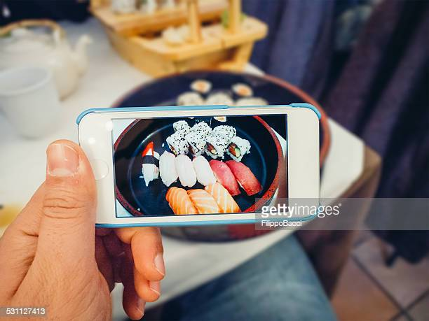 photographing sushi - sushi restaurant stock photos and pictures