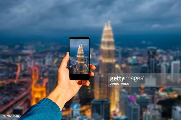 Photographing with smartphone in hand. Kuala Lumpur, Malaysia