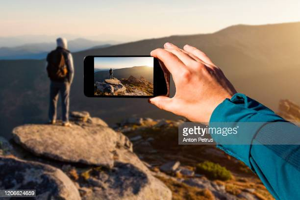 photographing with smartphone in hand. travel concept. man on top of a mountain watching the sunset - ukraine landscape stock pictures, royalty-free photos & images